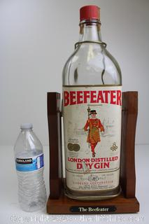 LARGE ONE GALLON GLASS BEEFEATER DRY GIN LIQUOR ON WOOD BASE AND CRADDLE